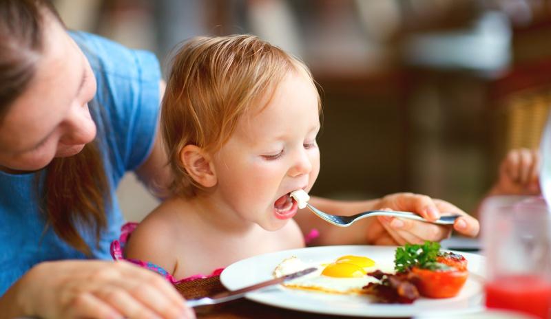 Crianca comendo ovo frito com a mae